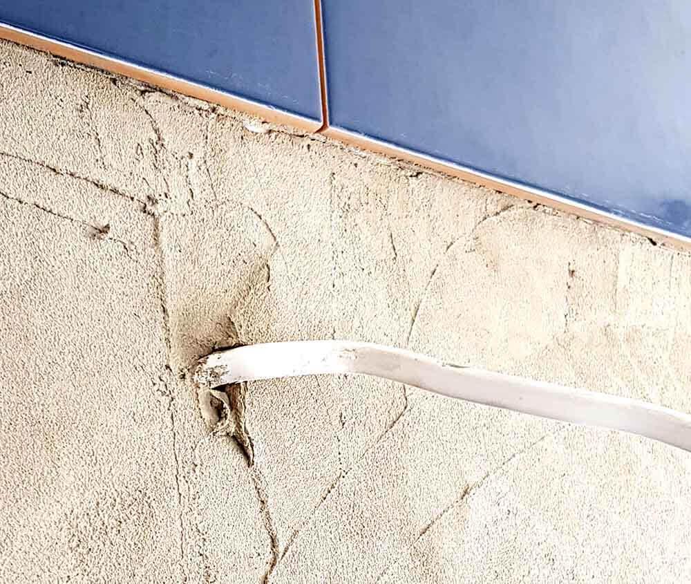 Przewód w ścianie zasilający kinkiet mocowany na lustrze.